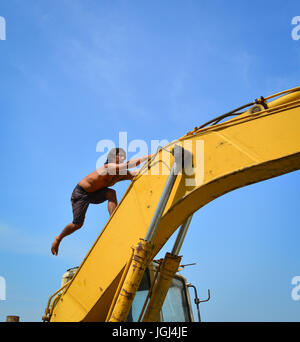 An Indian construction worker in relaxing hour at sunny day - Stock Photo