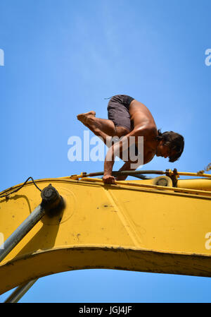 Indian worker doing yoga exercise on bulldozer at relaxing hour in the construction site - Stock Photo