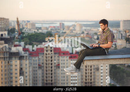 A hipster man with a laptop on the edge of the roof. Freelancer at work. Wireless Internet. He works on the Internet. - Stock Photo