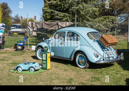 A Restored 1961 Volkswagen Beetle on display with a childs toy model VW and a small replica petrol bowser. - Stock Photo