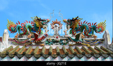 An image of dragon on a roof top of dragon Chinese temple. Dragon statue under blue dragon sky. - Stock Photo