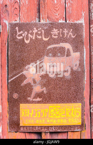 Japan, Tatsuno. Old vintage totally rusted Japanese kanji sign, warning of children chasing ball into road with - Stock Photo