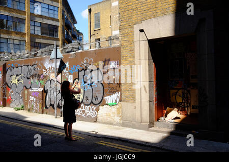 Person taking photographs of the graffiti in Corbet Place near Brick Lane, Shoreditch, London E1 using her smartphone - Stock Photo
