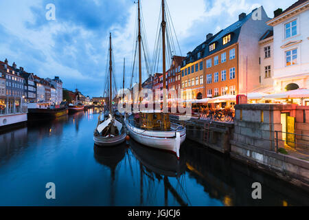Copenhagen Nyhavn (New Harbor) district with city lights after sunset during blue hour with wooden sailing ship - Stock Photo