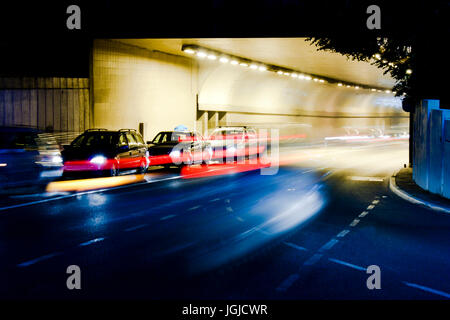 Night traffic on city streets.Cars at tunnel exit waiting at intersection while driving vehicles entering tunnel - Stock Photo