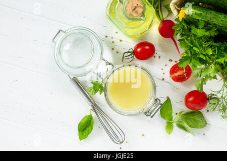 Homemade salad dressing vinaigrette with mustard and olive oil on a white kitchen wooden table. - Stock Photo