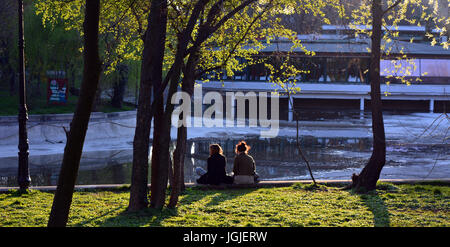 Two unrecognisable females sitting at the edge of the lake in the park Cismigiu in Bucharest, Romania. - Stock Photo