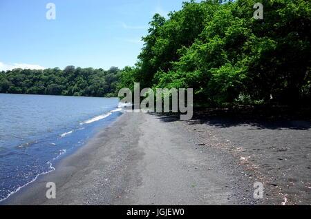 Black volcanic sand on a beach on Isla Ometepe - Stock Photo