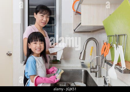 Asian Chinese little girl helping mother washing dishes in the kitchen at home - Stock Photo