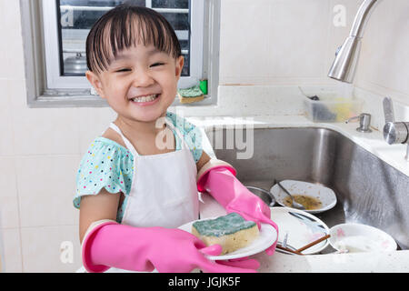 Asian Chinese little girl washing dishes in the kitchen at home - Stock Photo