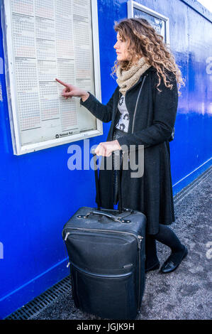 A pretty young woman, in winter clothing, holding a suitcase and pointing while viewing a train timetable at Abbey - Stock Photo