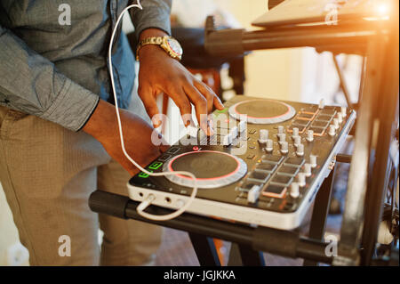 African american dj in huge white headphones creating music on mixing panel. - Stock Photo
