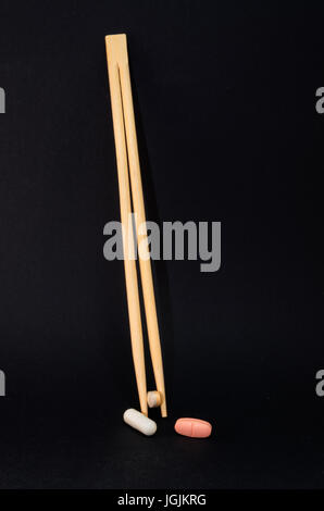 Chopsticks with tablets against a black background. Concept of health costs and drug misuse. - Stock Photo