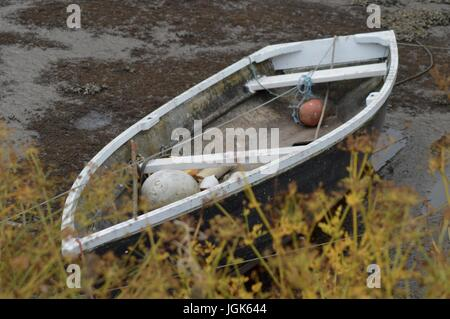 Rowing boat resting at low tide, creek  in Cornwall - Stock Photo