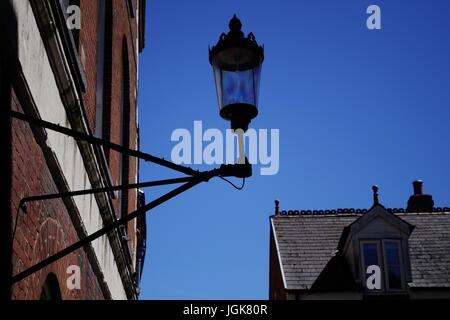 Old Wall Mounted Lamp in an Alley Way. Exeter, Devon, UK. July, 2017. - Stock Photo