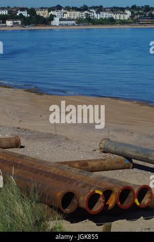 Metal Pipes Pilled on the Beach at Dawlish Warren for the Beach Management Scheme, Looking over towards exmouth. - Stock Photo