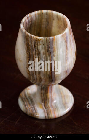 close up of a beautiful Onyx chalice on a dark wooden table - Stock Photo
