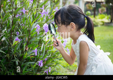 Asian Chinese little girl looking at flower through a magnifying glass in outdoor garden - Stock Photo