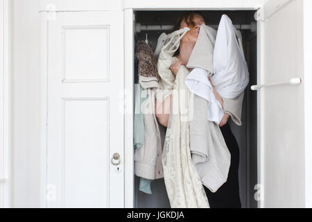 A woman is overwhelmed in closet of messy clothes - Stock Photo