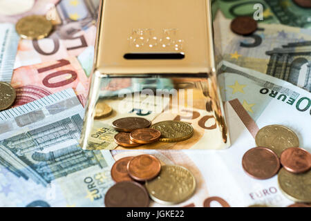 savings Cash money concept euro banknotes of all sizes and cent coins on desk piggy bank gold bar shape save - Stock Photo