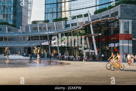 Milan, Italy - July 7th, 2017:  Office buildings in Piazza Gae Aulenti, a popular place to enjoy a coffee and aperitivo - Stock Photo