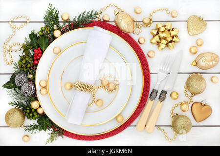 Christmas dinner place setting with porcelain plates, gold bauble decorations, holly, mistletoe, ivy and fir on - Stock Photo