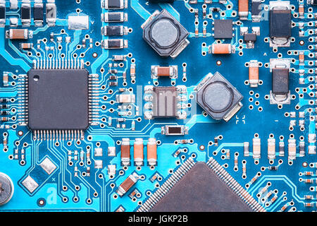 macro top view of a printed circuit board with processors, capacitors and transistors - Stock Photo