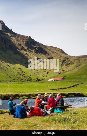 Family picnic on the banks of the Skoga River below the Skogafoss waterfall in Iceland - Stock Photo