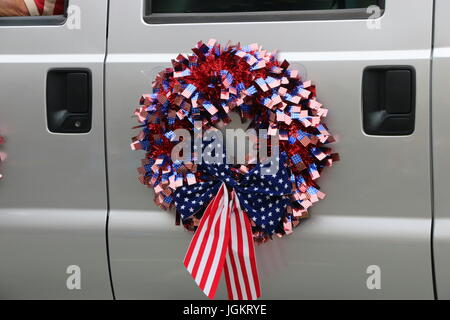 American flag wreath on car in parade. - Stock Photo
