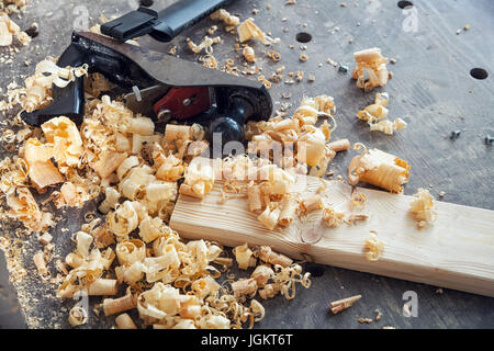 A black jack plane for a tree lies on a wooden table around a lot of wooden sawdust - Stock Photo