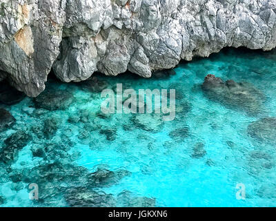 Wonderful turquoise sea with clean and transparent water under rock cliff at Castro Marina, Salento, Italy. - Stock Photo