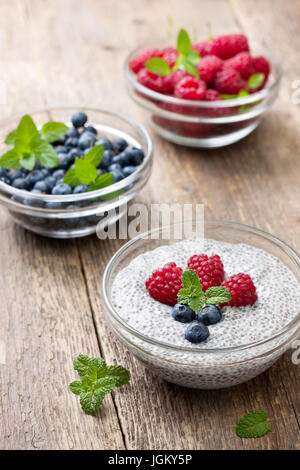 chia pudding with raspberries and blueberries in a glass bowl, fresh berries on old wooden background - Stock Photo