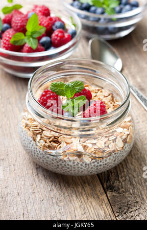 Healthy dietary breakfast. Chia pudding with muesli, raspberries, blueberries in a glass bowl, fresh berries on - Stock Photo