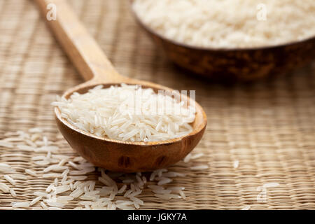 Basmati rice in wooden spoon on straw background - Stock Photo