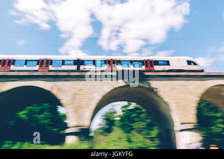 Geneva, Switzerland - June 25, 2017: Swiss regional train passing over a bridge in the Geneva Canton region, with - Stock Photo