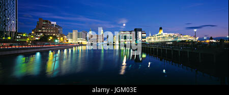 Panorama of Princes Dock Liverpool at night showing cruise liner berthed at Liverpool cruise terminal. - Stock Photo