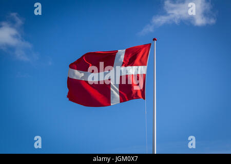 Danish flag in sunshine against blue sky with clouds, horizontal - Stock Photo