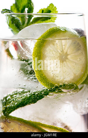 Gin tonic cocktail with lime, lemon ice and mint, white background. Close up detail - Stock Photo