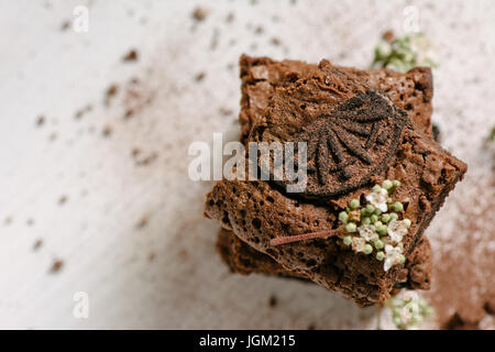 Chocolate brownies, with black biscuit stuffed with cream, stacked from above - Stock Photo