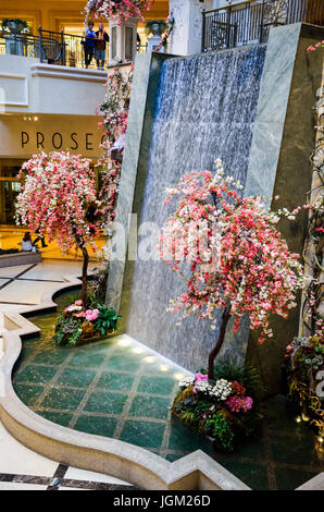 Las Vegas, USA - May 7, 2014: Venetian hotel fountain decorated with flowers on trees inside mall in Nevada - Stock Photo