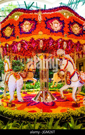 Las Vegas, USA - May 7, 2014: Wynn hotel decorated with rose flowers and carousel with horses inside mall in Nevada - Stock Photo