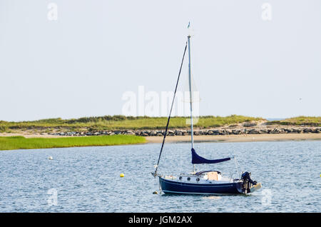 Wellfleet, USA - July 30, 2014: Empty sail boat in ocean water at Cape Cod with person walking on beach - Stock Photo