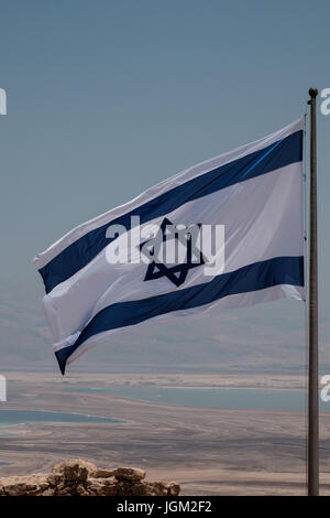 Israel flag waving in the wind on top of the masada fortress in Israel, a symbol of hope and a proof of our triumph - Stock Photo