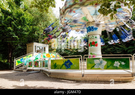 A chair swing ride carousel with flying chairs in a park. - Stock Photo