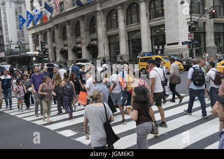 The always crowded corner at 5th Avenue and 34th Street by the Empire State Building is constantly full of tourists - Stock Photo