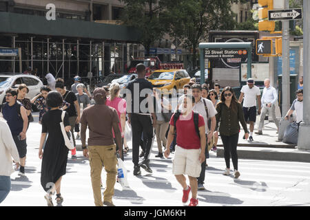 The always busy Chelsea neighborhood at 23rd Street and 6th Avenue in Manhattan. - Stock Photo