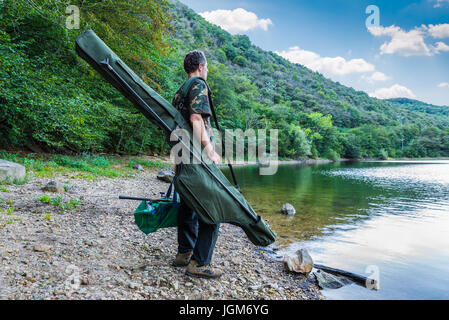 Fishing adventures, carp fishing. Fisherman on a lake shore with camouflage fishing gear, green bag and mimetic - Stock Photo