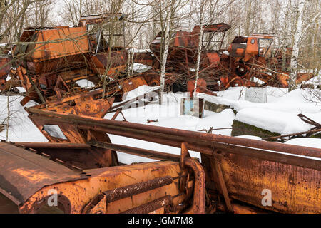 Rusty metal threshers in Chernobyl in the Exclusion zone in the Ukraine in wintertime. - Stock Photo