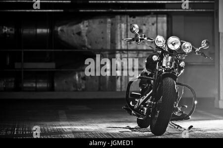 motorbike parked in the garage. Modified Harley Davidson Bobber parked in underground garage. - Stock Photo
