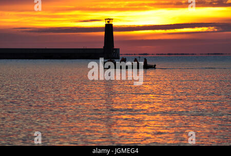 Lighthouse and fishing boat silhouette during bright summer sunrise over the baltic sea in Gdynia, Poland - Stock Photo